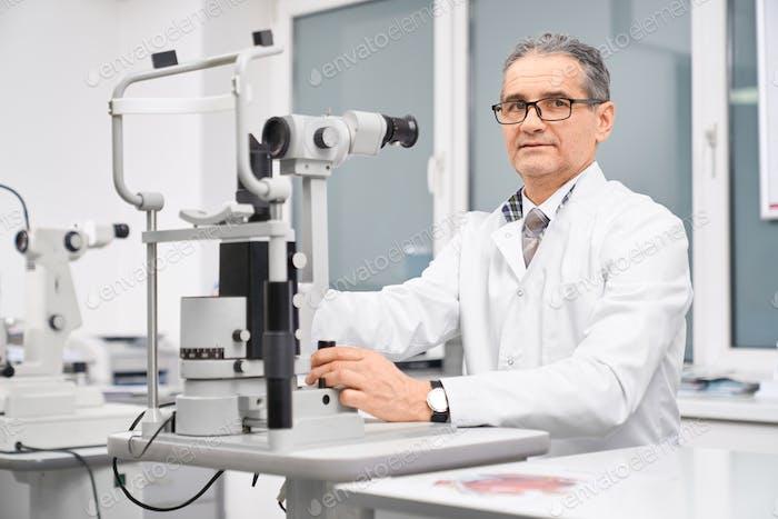 Augenarzt posiert mit Spaltlampe im Schrank