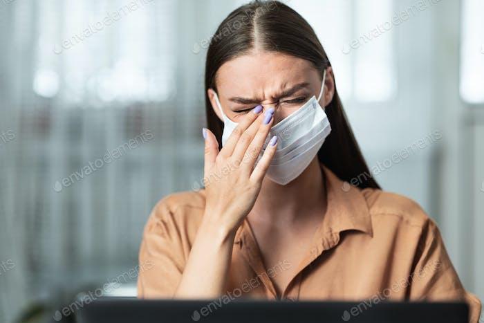 Portrait of woman in quarantine wearing mask touching eye
