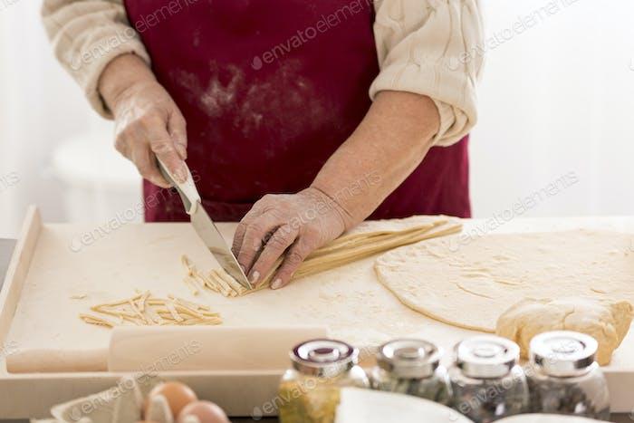 Grandmother preparing traditional pasta