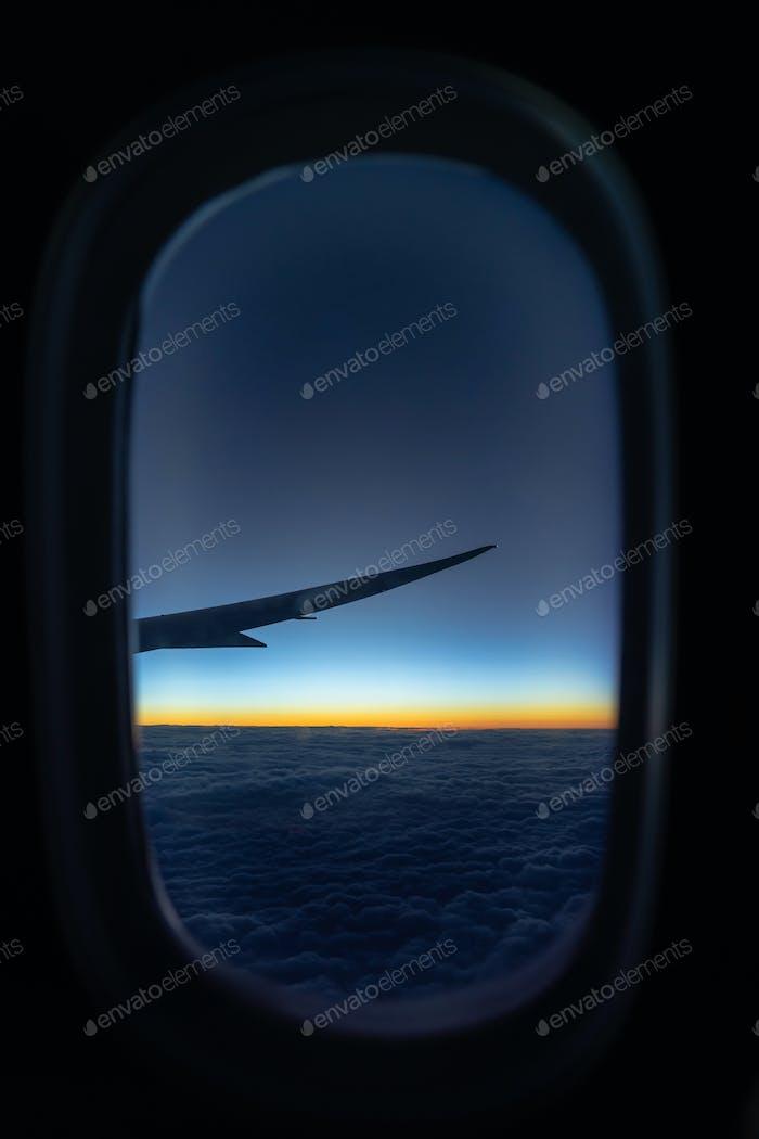 Szene des Flugzeugs über die Wolke und fantastischer Himmel bei Sonnenaufgang beim Fliegen über dem Land,