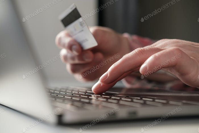 Female hands enter bank details of a credit card on a laptop to pay for online purchases.
