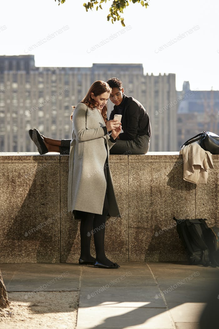 Two female friends taking a break on the embankment, looking at a smartphone