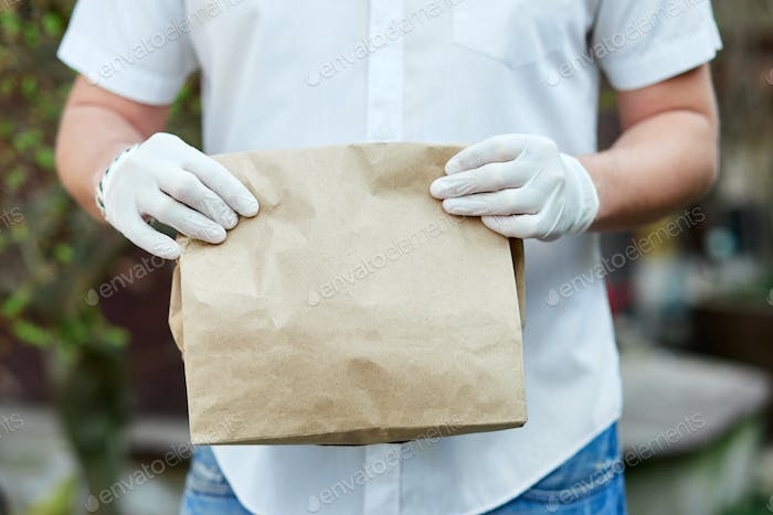 Courier, delivery man delivers online purchases during the coronavirus epidemic.
