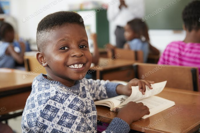 Boy at desk smiling to camera in an elementary school lesson