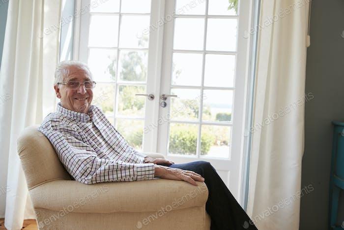 Senior man sitting in an armchair turns smiling to camera