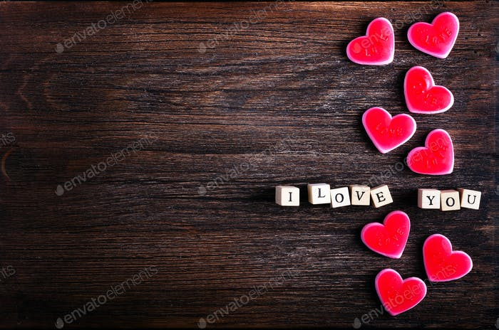 Heart shaped chewing candies and words I love you on cubes, wooden background. Free space for your