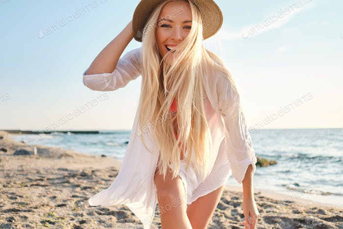 Joyful blond woman in swimsuit and white shirt wearing hat happily looking in camera by the sea