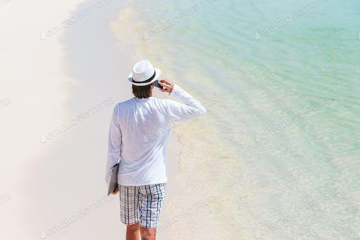 Young man at tropical beach near water villa