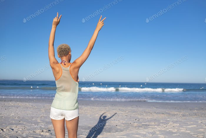 Rear view of African american woman standing with arms up on the beach
