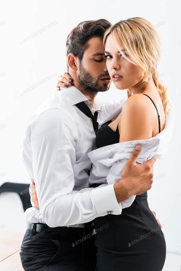 Businessman hugging seductive colleague on office table