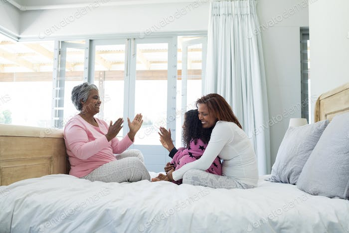 Family playing clapping games on bed in bedroom