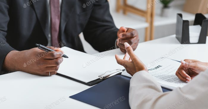 Unrecognizable HR manager interviewing potential employee at office, close up view