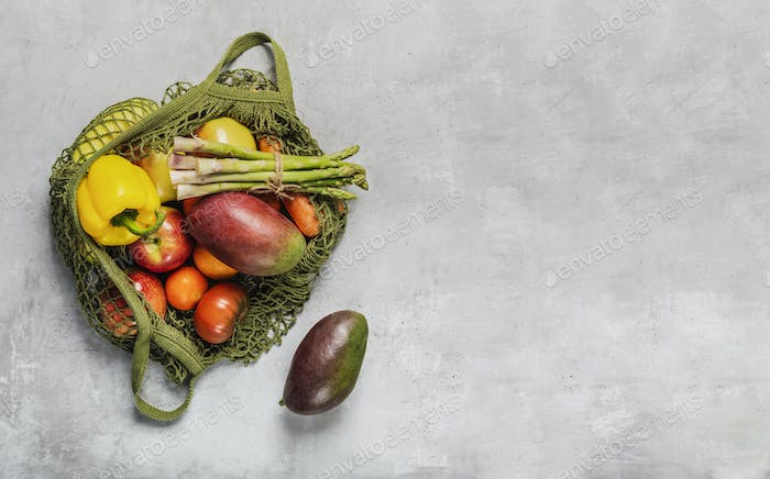 Fresh vegetables and fruits in a green string bag