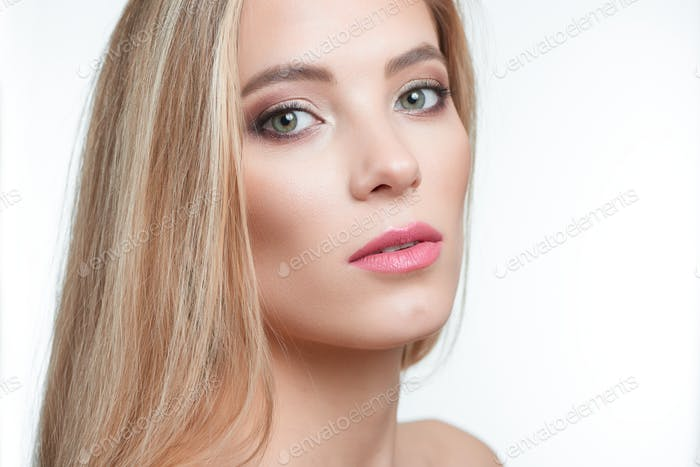 Half profile portrait of a blonde green-eyed model with makeup on