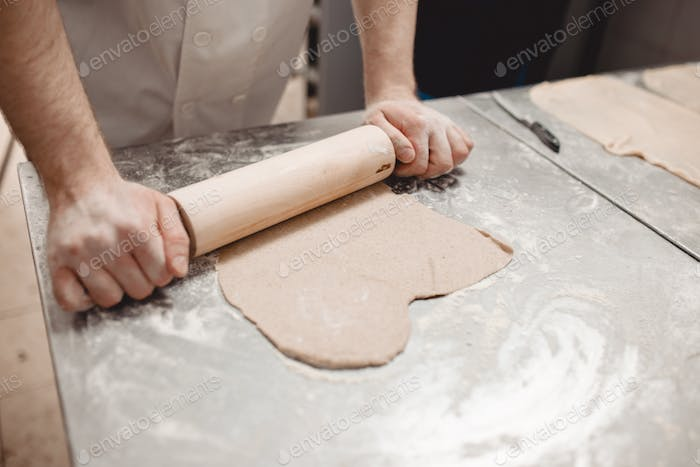 Baker is rolling dough on the table in the bakery