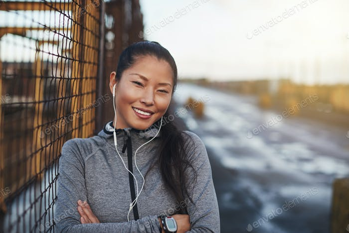 Asian woman in sportswear listening to music before a run