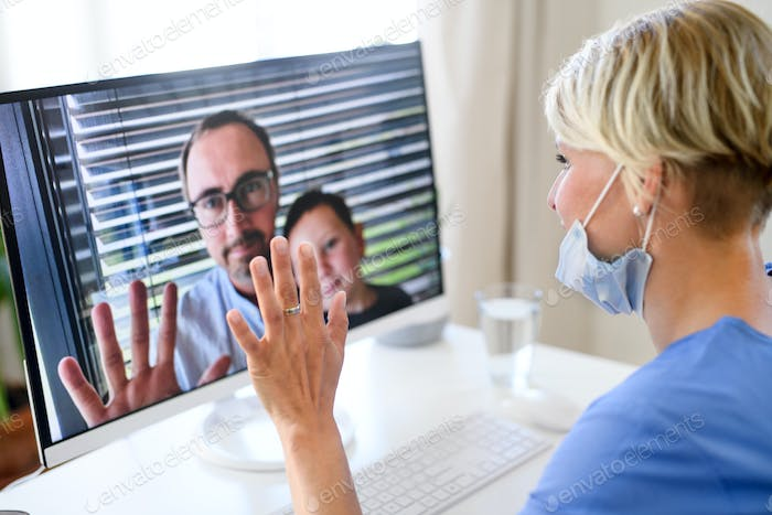 Woman doctor having video call with husband and son on laptop