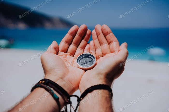Open hand palms with metal compass on the sandy beach. Searching your way concept. Blue sea in