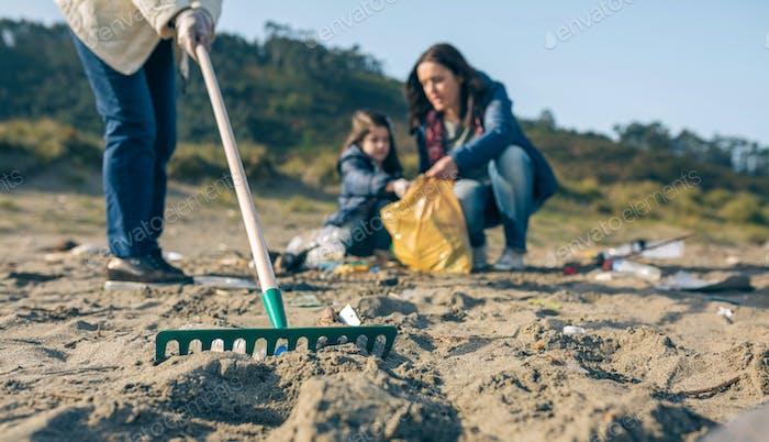 Rake with volunteer women cleaning the beach