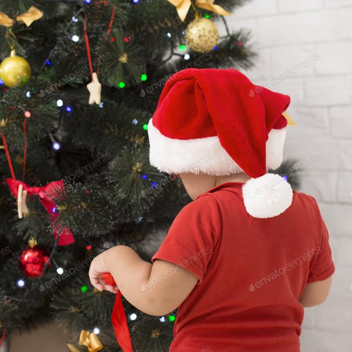 Little baby decorating Christmas tree at home