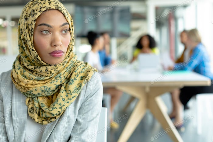 Thoughtful Mixed-race businesswoman in hijab looking away