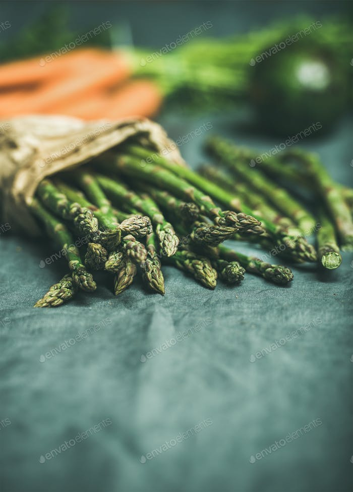Green asparagus, carrots and avocado at background over linen table