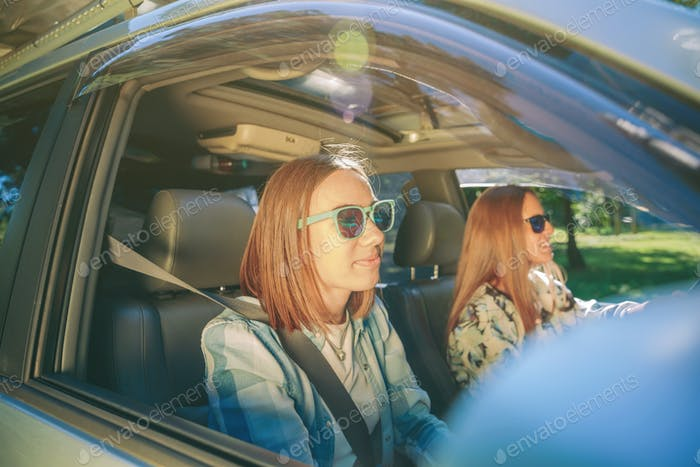 Zwei glückliche junge Frauen reisen im Auto