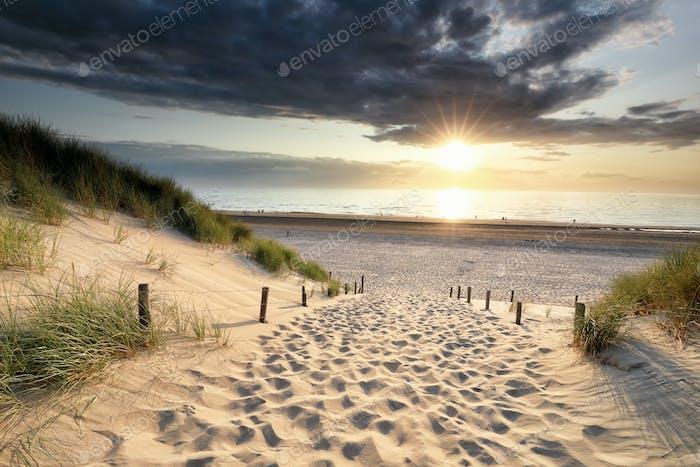 path on sand to North sea beach at sundown
