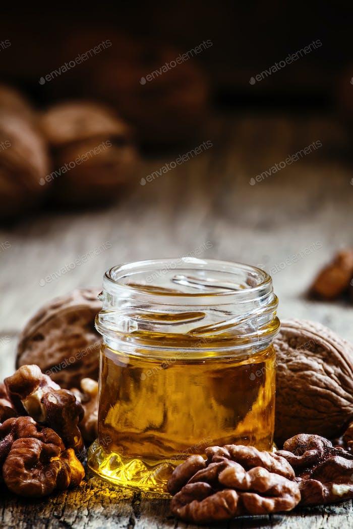 Walnussöl in einem kleinen Glas und Kernen