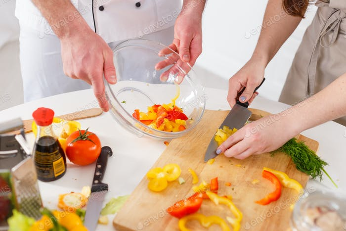 Woman mixing a salad with professional cook in the kitchen