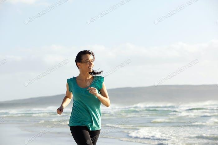 activa joven Mujer disfrutando de un correr en el Playa