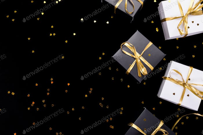 black and white gift boxes with gold ribbon on shine background