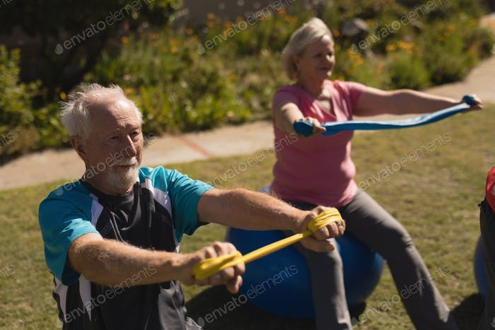 Front view of active senior man and woman exercising with elastic band and ball in park