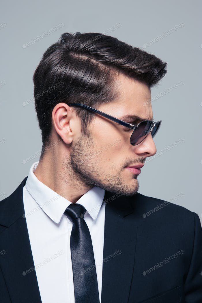 Businessman in sunglasses looking away