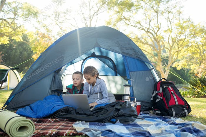 Kids using laptop in the tent