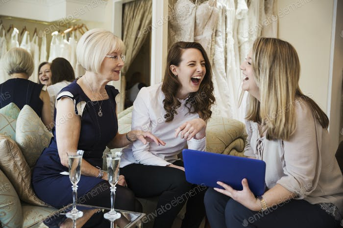 Three women in a wedding dress shop, one bride to be and two retail advisors looking at a digital