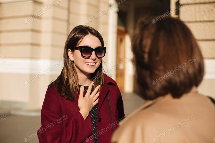 Young smiling lady in sunglasses standing and happily talking with friend on street