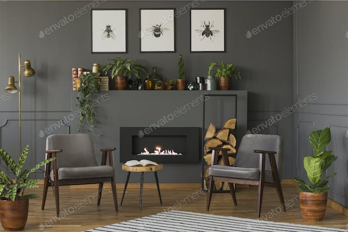 Wooden table between grey armchairs in retro flat interior with