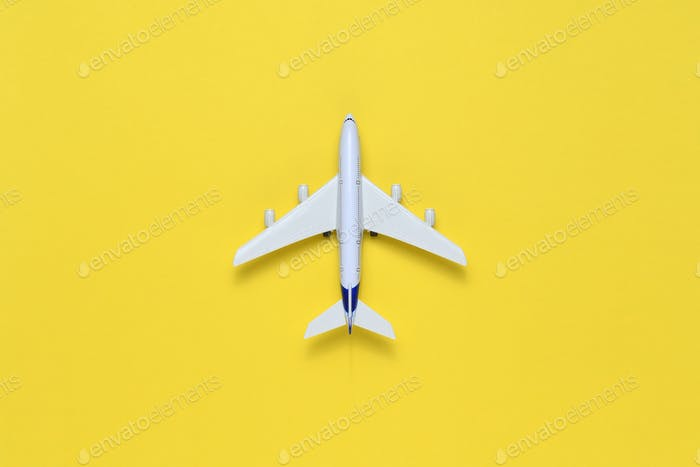 Toy airplane on yellow table top view