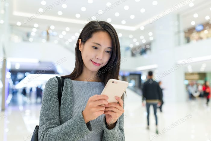 Woman use of mobile phone in shopping plaza