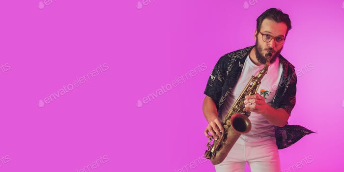 Young caucasian jazz musician playing the saxophone in neon light, flyer with copyspace for ad