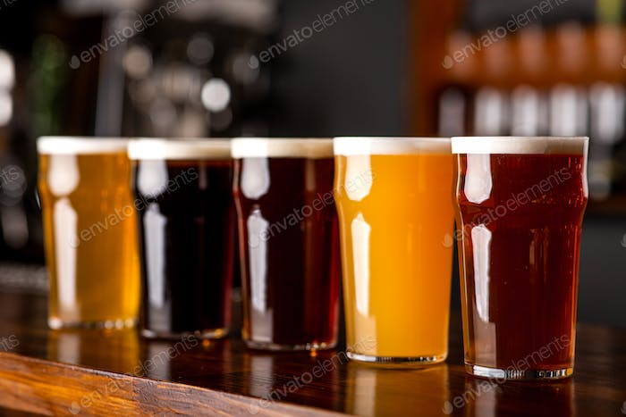 Dark, light, barley, lager and ale in glasses on bar counter