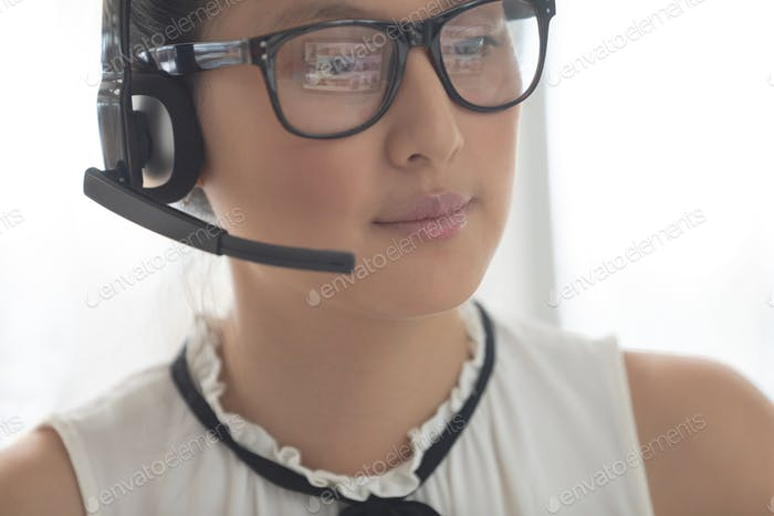 Beautiful Asian female customer service executive with headset looking away