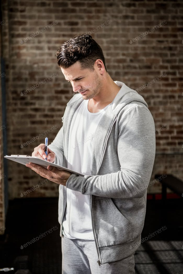 Muscular man writing on clipboard at the gym
