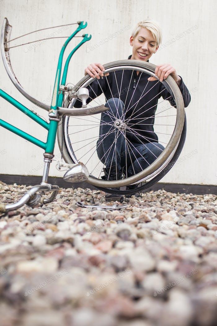 Glückliche weibliche Mechaniker Reparatur Fahrrad außerhalb Werkstatt