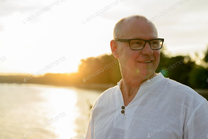 Mature handsome tourist man against view of the beach outdoors