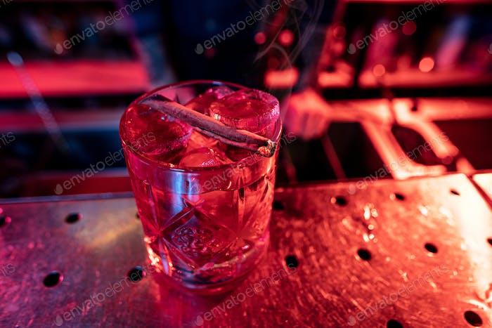 Nahaufnahme von alkoholischen Cocktail, Getränken, Getränken, Glas voller Eis in mehrfarbigem Neonlicht
