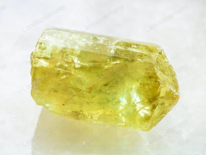 raw crystal of yellow Apatite gemstone on white