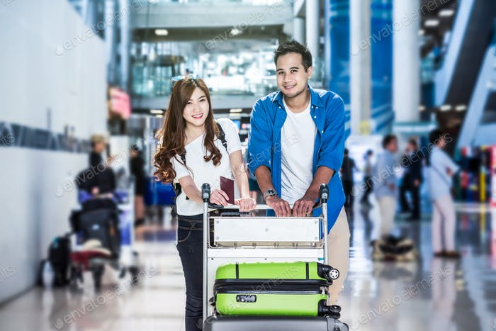 Asian couple traveler with suitcases at the airport. Lover travel and transportation