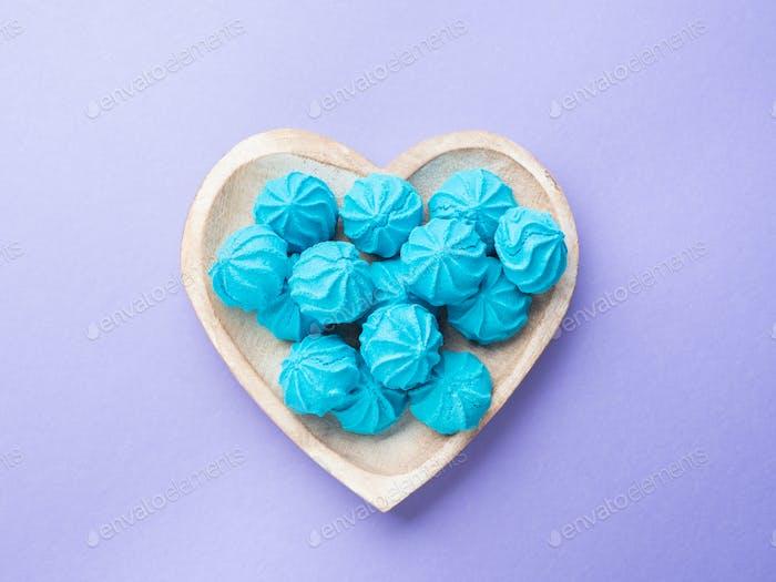 Herzförmige Holzschale mit blauen süßen Baisers